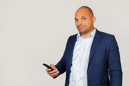 Portrait young african american businessman guy, uses smartphone with confident expression on smart face, reads message seriously thinking. Standing on a gray background