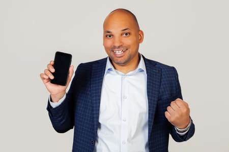 Portrait of happy young african american businessman guy, shows smartphone screen, shouts with pride and celebrates victory and success, very excited, rejoices in emotions. Standing on a gray background