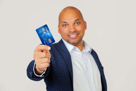 Portrait of a happy young African American businessman guy holding a credit card with a happy face, stands and smiles with a confident smile showing teeth. Standing on a gray background