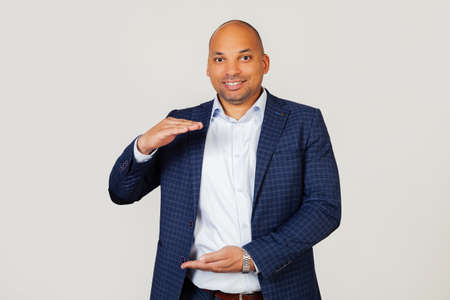 Portrait of happy young african american businessman guy gesturing with hands showing big and large size sign, symbol of measure. Smiling looking into the camera. Standing on a gray background Foto de archivo