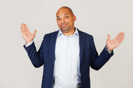 Portrait of doubtful young african american businessman guy, gesturing with hands, ignorant and confused expression with raised hands and arms. Doubt concept. Standing on a gray background
