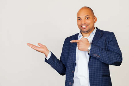Portrait of happy young African American businessman guy, amazed and smiling at the camera, showing with hand and pointing with finger. Standing on a gray background