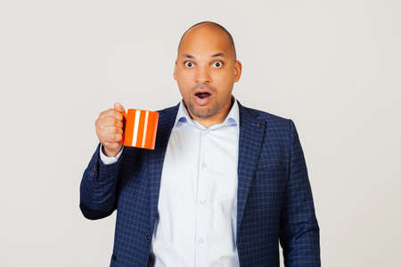Portrait of astonished young African American businessman guy, holding a cup of coffee in his hand, scared shocked with a surprised face, scared and excited with an expression of fear. gray background