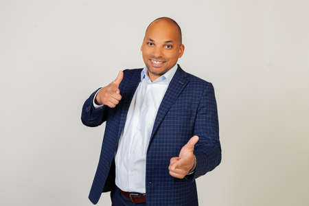 Portrait of a successful young African American businessman guy pointing his fingers at the camera with a happy and funny face. Good energy and vibes. Standing on a gray background