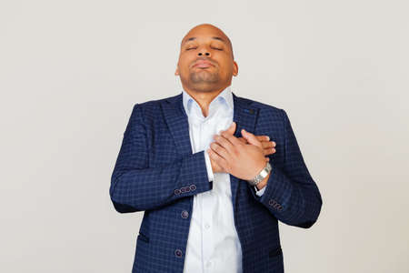 Portrait of grateful young African American businessman guy smiling with hands on chest with closed eyes and grateful gesture on face. Health concept. Standing on a gray background. Foto de archivo