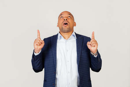 Portrait of astonished young African American businessman guy, amazed and surprised, looking up and pointing with fingers and raised hands. Standing on a gray background Foto de archivo