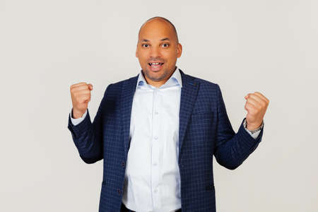 Portrait of a successful young African American businessman guy, very happy and excited, making a winner gesture with raised hands, smiling and shouting success. Celebration concept. Gray background
