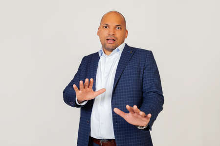 Portrait of shocked young African American businessman guy, scared and frightened by fear expression, stopped hand gesture, shouting in shock. Panic concept. Standing on a gray background