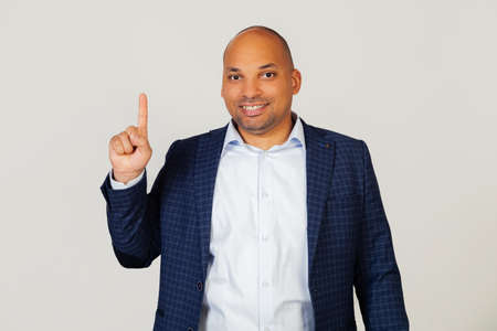 Portrait of successful young African American businessman guy, showing number one fingers, smiling, confident and happy. The man shows one finger. Number 1 Standing on a gray background