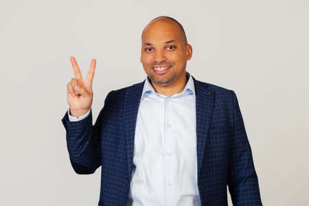 Portrait of a successful young African American businessman guy, showing with fingers to number two, smiling, confident and happy. The man shows two fingers. Number 2. Standing on a gray background