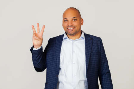 Portrait of a successful young African American businessman guy, showing with fingers to number three, smiling, confident and happy. The man shows three fingers. Number 3. Standing on a gray background