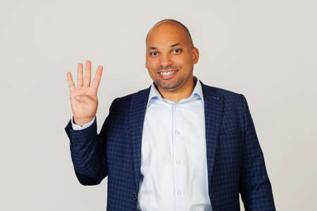 Portrait of a successful young African American businessman guy, showing with fingers to number four, smiling, confident and happy. The man shows four fingers. Number 4. Standing on a gray background Foto de archivo