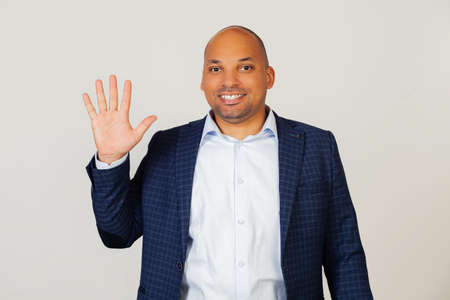Portrait of successful young African American businessman guy, showing with fingers number five, smiling, confident and happy. The man shows five fingers. Number 5. Standing on a gray background