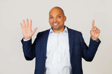 Portrait of successful young African American businessman guy, showing number six with fingers, smiling, confident and happy. The man shows six fingers. Number 6. Standing on a gray background