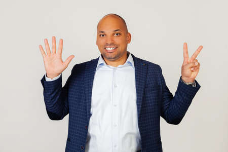 Portrait of successful young African American businessman guy, showing with fingers to number seven, smiling, confident and happy. The man shows seven fingers. Number 7. Standing on a gray background Foto de archivo