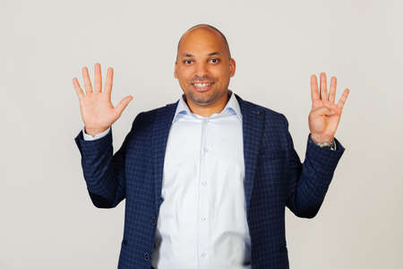 Portrait of successful young African American businessman guy, showing with fingers to number nine, smiling, confident and happy. The man shows nine fingers. Number 9. Standing on a gray background Foto de archivo