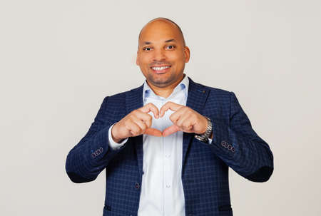 Portrait of a romantic young African American businessman guy smiling in love showing heart symbol and shape with hands. Romantic concept. Standing on a gray background