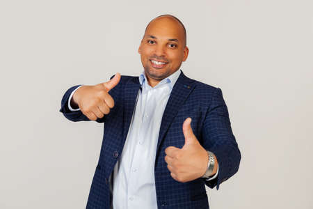 Portrait of a successful young African American guy businessman making a positive hand gesture approvingly, smiling thumbs up and happy for success. Winners gesture. Standing on a gray background