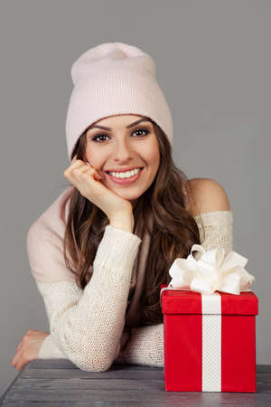 Smiling and happy, beautiful young woman in winter clothes with a red Christmas gift box on a gray background. The girl enjoys Christmas shopping, meets the New Year. Shopping sale concept.