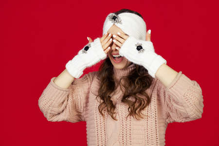 Smiling and happy, beautiful young woman in winter clothes covering her eyes with her hands, waiting for a Christmas present. New Years surprise. Standing on a red background.