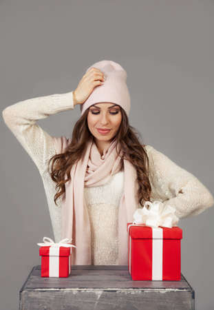 A beautiful young woman cannot decide which gift to choose, looks at a small and large box. The girl makes Christmas shopping, meets the New Year. Shopping sale concept Foto de archivo