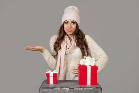 A beautiful young woman in winter clothes, thoughtfully, hesitantly, stands before the choice of a small or large gift for the New Year and Christmas. The girl decides which gift to choose Banque d'images