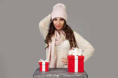 A beautiful young woman in winter clothes, thoughtfully, hesitantly, stands before the choice of a small or large gift for the New Year and Christmas. The girl decides which gift to choose Foto de archivo