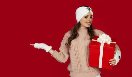 Beautiful happy woman with red gift box and points with her hand to the side, winter holidays atmosphere. Girl holding Christmas shopping, greets New Year. Shopping sale concept