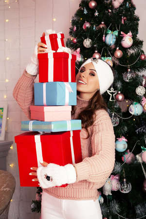 Smiling and happy, young woman in winter clothes holds many wrapped gift boxes in front of her near the Christmas tree. Girl enjoy Christmas gifts, greet New Year and Christmas, holidays concept.