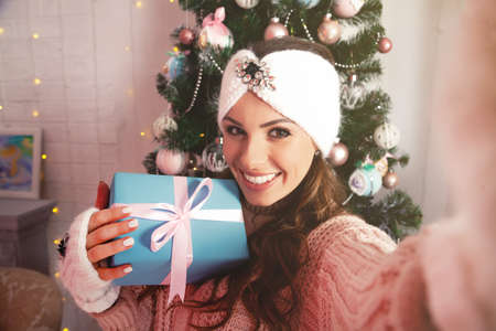 Self-portrait of a cheerful rejoicing girl removing a gift box with a Christmas tree behind her back. Young woman in winter clothes makes a photo with a gift for New Year and Christmas