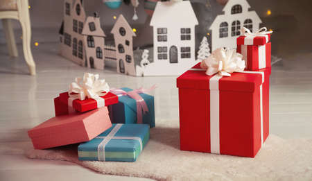 Beautiful Christmas gift boxes on the floor near the Christmas tree in the room. Holidays, gifts, new year and celebration concept - gift boxes on sheepskin. Stack of wrapped christmas gifts.