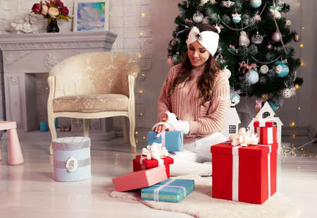 Smiling and happy young woman in winter clothes sitting comfortably on the floor near the Christmas tree opens a New Years present. The girl enjoys Christmas gifts, meets the New Year and Christmas