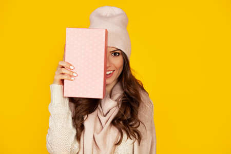 Happy young woman with a gift box in her hands, covers half of her face with a New Years gift. The girl shows a gift to the camera. The concept of gifts and surprises for the new year and christmas.