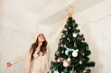 Happy young woman decorates the Christmas tree. A girl in a sweater sets a star on top of a Christmas tree. New year and christmas holiday concept Foto de archivo