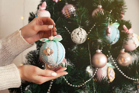 Close-up of female hands hang the ball on the tree. Christmas decoration, toys hanging on the tree, Christmas tree ball. New year and christmas holiday concept