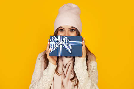 Happy young woman with a gift box in her hands, covers half of her face with a New Year's gift. The girl shows a gift to the camera. The concept of gifts and surprises for the new year and christmas. Foto de archivo