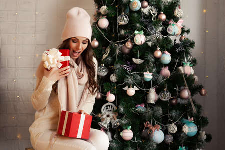 Smiling and happy, beautiful young woman in winter clothes with a red Christmas gift box on the background of a decorated Christmas tree. The girl delightedly opens the gift, greets the New Year.