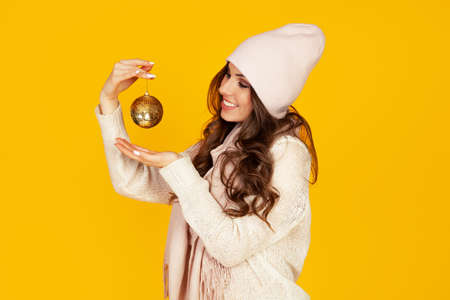 Happy young smiling woman holding a christmas tree ball promoting a best offer christmas tree. A girl in a sweater looks at a Christmas tree toy. New year and christmas holiday concept