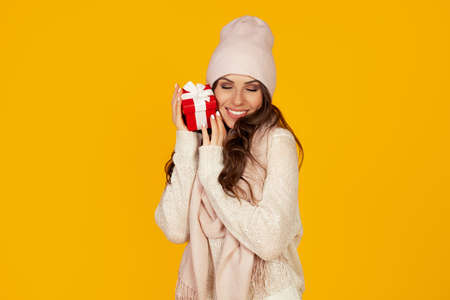 A portrait of an outspoken contented girl enjoys a gift box she receives for the New Year and Christmas. A woman holds a red gift box on a yellow background. Gifts for the holiday.