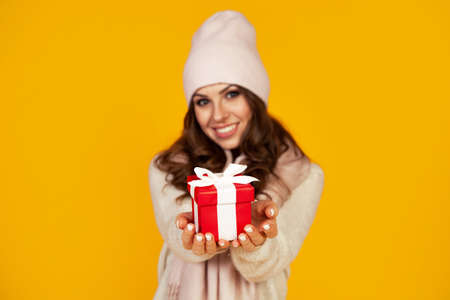 Happy young smiling woman holding and holding red gift box in front, offering and giving Christmas gifts. A girl in a sweater looks at the camera and gives a gift. Christmas New Year holiday concept