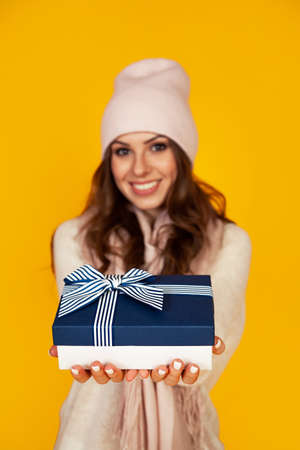 Happy young woman smiling, holding and stretching in front gives a blue gift box to her beloved man a Christmas present. A girl in a sweater looks at the camera and gives a gift
