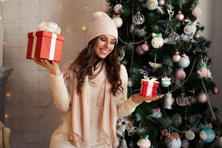 Smiling and happy young woman in winter clothes sitting comfortably on the floor near the Christmas tree opens a New Year's present. The girl enjoys Christmas gifts, meets the New Year and Christmas