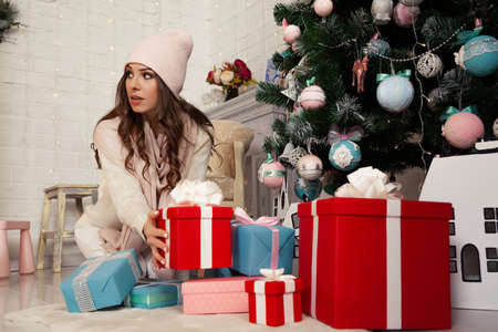 Happy young woman putting gift boxes under the Christmas tree. Gifts for the family. The girl in the sweater is preparing a surprise. Christmas New Year holiday concept