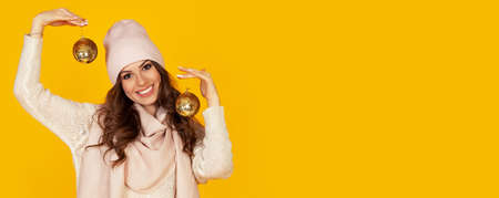 Happy young smiling woman holding Christmas balls, offering Christmas shopping sale. The girl in a sweater looks into the camera while holding Christmas toys. New year and christmas holiday concept Foto de archivo
