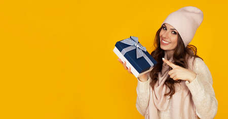 Happy young woman smiling pointing finger holding blue gift box in hand. A gift to your beloved man. A girl in a sweater looks at the camera and points to a gift. Christmas New Year holiday concept
