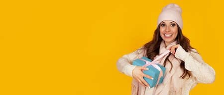 Happy young woman with open mouth opening a gift box of Christmas present, Girl looks into the gift box and laughs with happiness. The concept of gifts and surprises for the new year and christmas