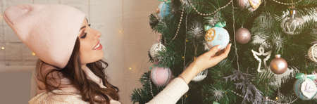 Happy young woman decorates the Christmas tree. Girl in a sweater decorating a Christmas tree with balls. New year and christmas holiday concept