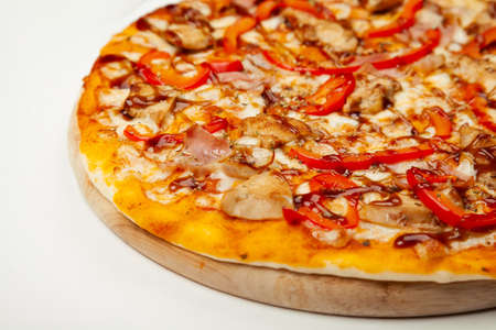 Delicious pizza with bacon and chicken Teriyaki served on a wooden plate, ingredients Signature sauce, mozzarella cheese, Teriyaki chicken, bacon, Bulgarian pepper, Teriyaki sauce on white