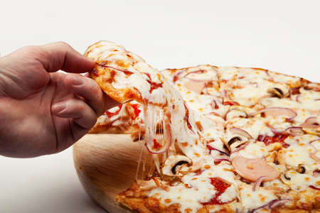 Mans hand takes a delicious slice of pizza with Margarita or Margarita with Mozzarella cheese, A man takes a slice of Italian pizza and pulls out an appetizing melted cheese.