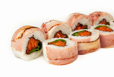 Sushi roll with bacon and salmon on a white background, ingredients seared bacon, salmon, green onions, flying fish roe, Iceberg sauce, rice, nori. Traditional Japanese food. For the restaurant menu